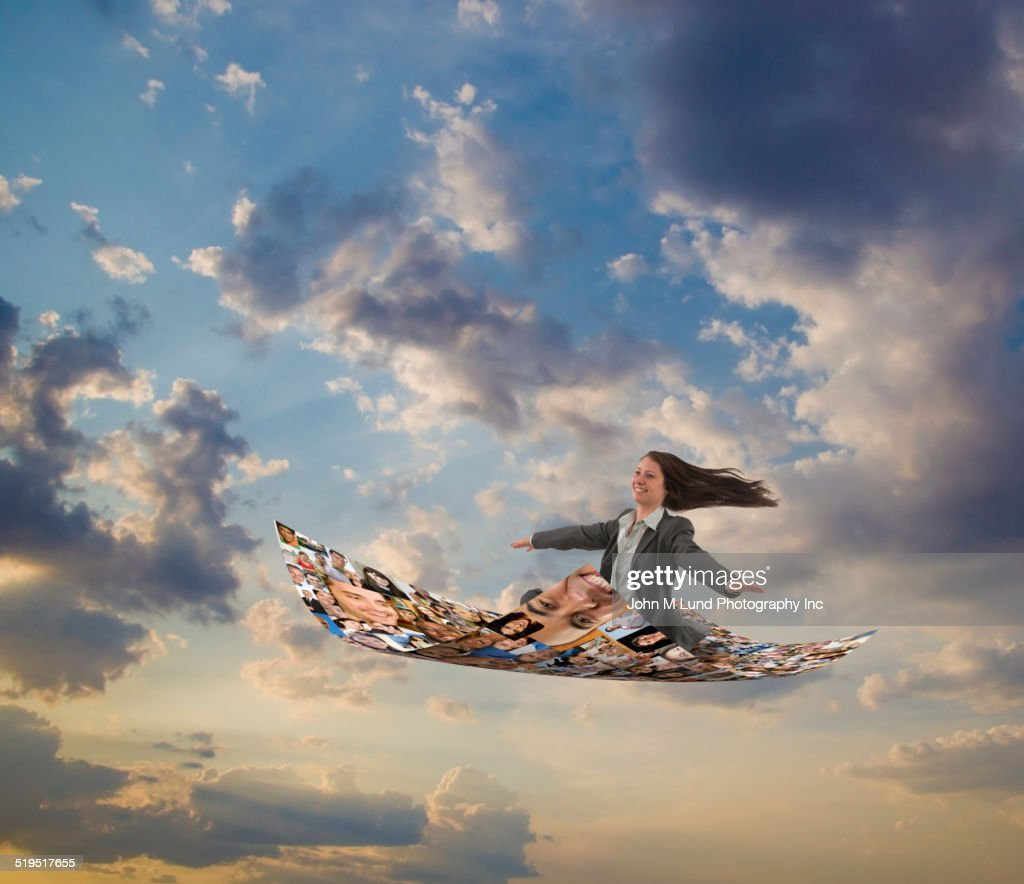 Businesswoman flying on carpet of images of smiling faces : Stock Photo