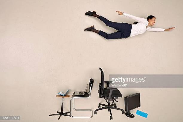 businesswoman flying over chairs and devices - hovering stock pictures, royalty-free photos & images
