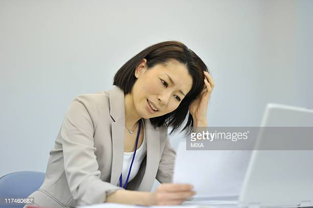 Businesswoman frowning at office