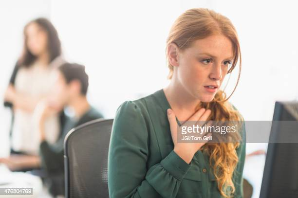 Businesswoman gasping at computer in office