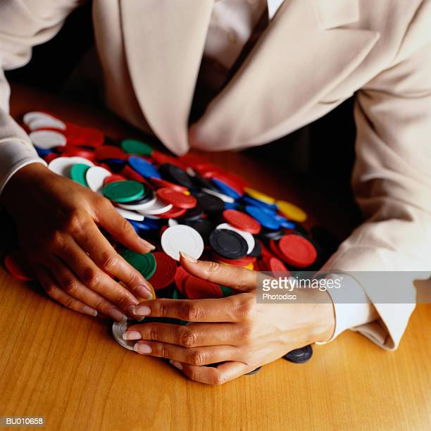 Businesswoman Gathering a Pile of Poker Chips