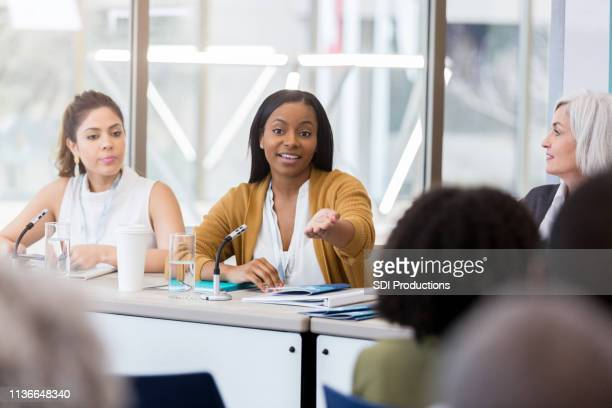 businesswoman gestures during panel discussion - panel discussion stock pictures, royalty-free photos & images