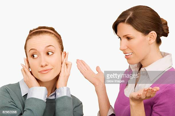 businesswoman gesturing with her colleague ignoring her - fingers in ears stock pictures, royalty-free photos & images