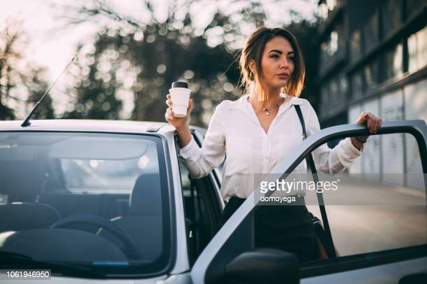 businesswoman getting coffee in the morning and entering car - rush hour stock pictures, royalty-free photos & images