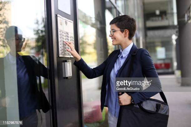 businesswoman getting into a building - intercom stock pictures, royalty-free photos & images