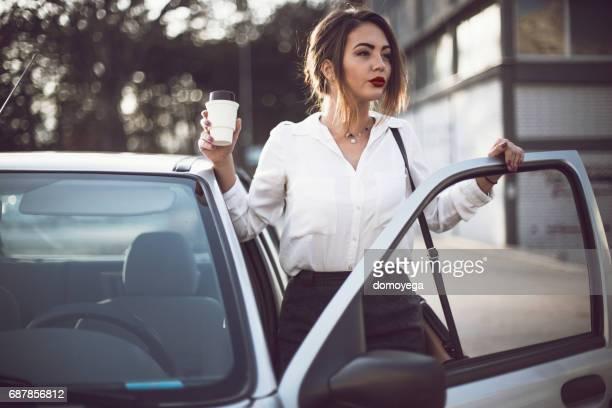 Femme d'affaires entrer dans la voiture et transportant la tasse de café