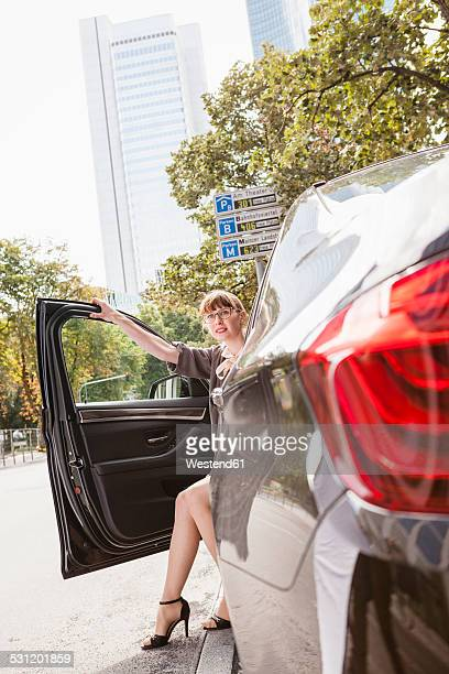Businesswoman getting off her car