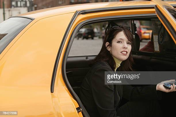 Businesswoman getting out of taxi holding PDA