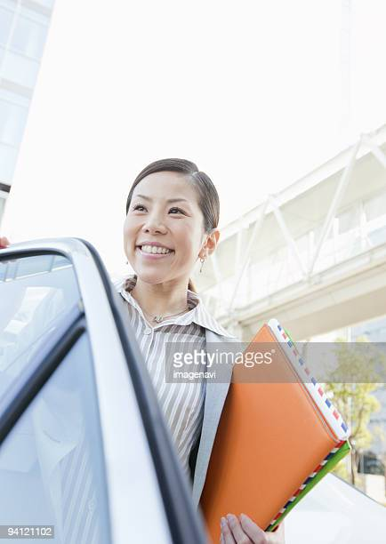 Businesswoman getting out of taxi