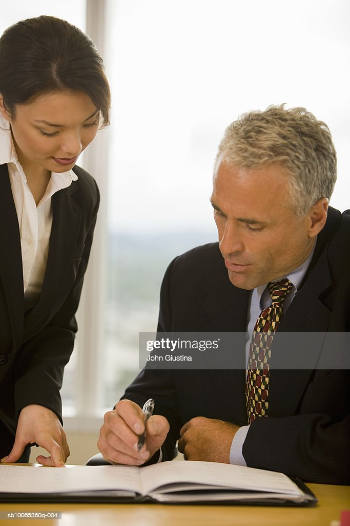 Businesswoman getting signature on document from businessman : Foto stock