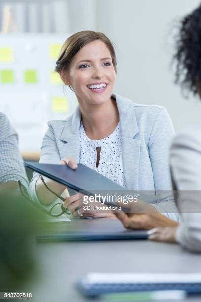 Businesswoman gives a colleague a portfolio during meeting