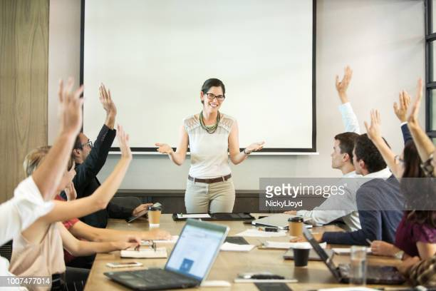 businesswoman giving a presentation to a group of people in a boardroom - sports league stock pictures, royalty-free photos & images