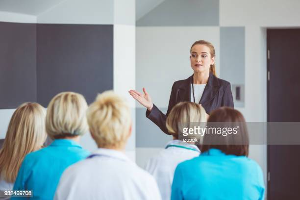 businesswoman giving a speech on seminar for medical staff - presenter stock pictures, royalty-free photos & images