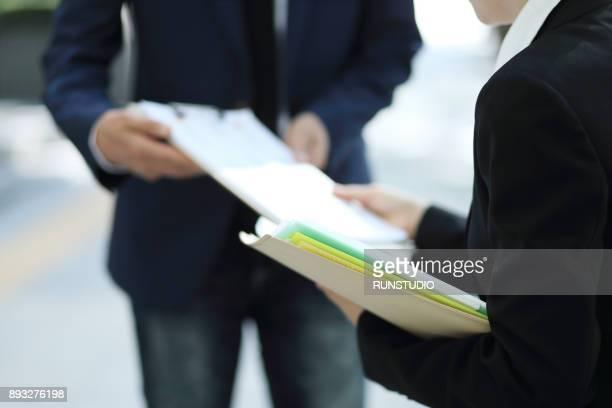 businesswoman giving paperwork to manager - oferecer imagens e fotografias de stock