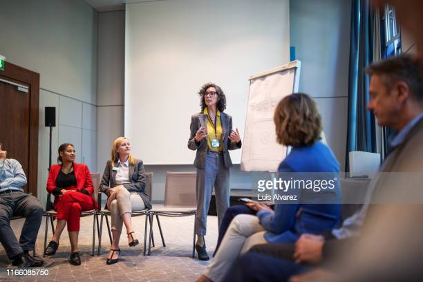 businesswoman giving presentation during a seminar - seminario riunione foto e immagini stock