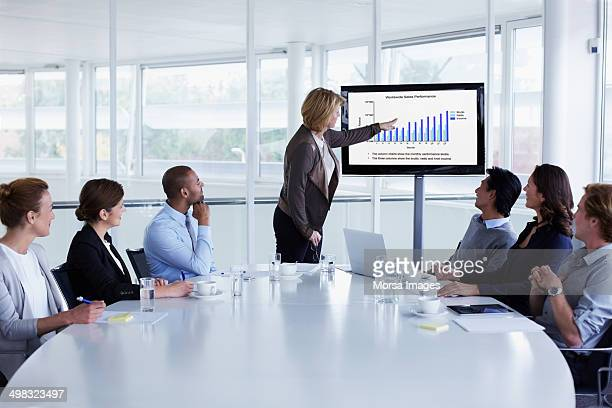 businesswoman giving presentation in meeting - tonen stockfoto's en -beelden