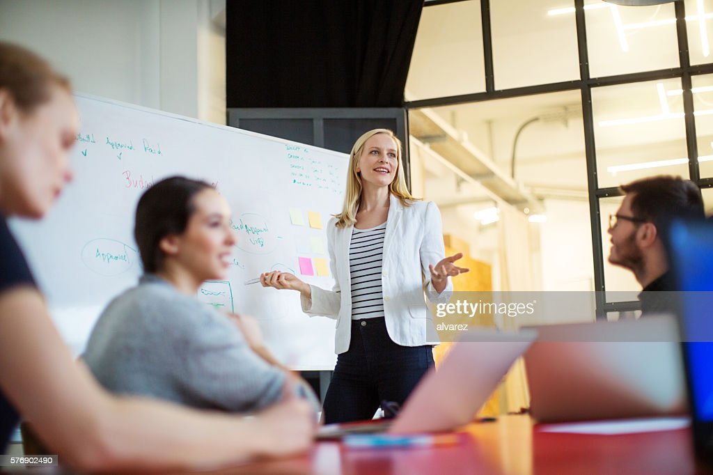 Businesswoman giving presentation on future plans to colleagues : Stockfoto
