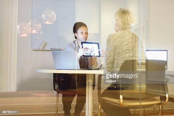 businesswoman giving presentation to colleague on digital tablet in office - werkneemster stockfoto's en -beelden