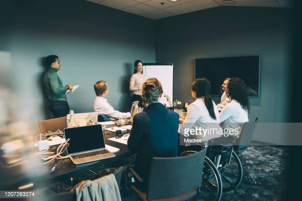 businesswoman giving presentation to colleagues during meeting in board room at office - differing abilities female business fotografías e imágenes de stock