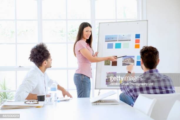 Businesswoman giving presentation to colleagues in conference