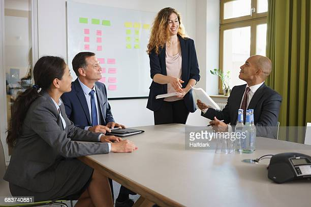 Businesswoman giving presentation to colleagues in meeting at conference table