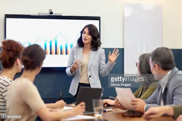 businesswoman giving presentation to colleagues - apresentação discurso imagens e fotografias de stock