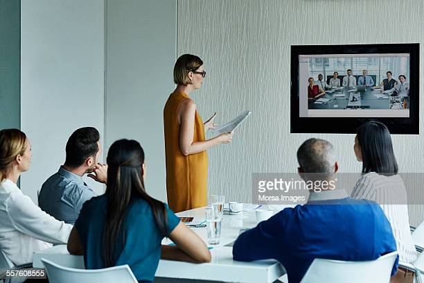 businesswoman giving presentation to colleagues - 21st century stock pictures, royalty-free photos & images