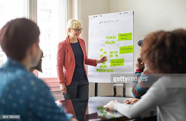 businesswoman giving presentation to her colleagues - giving stock photos and pictures