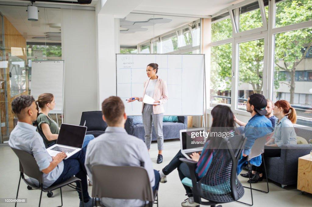 Businesswoman giving presentation to team : Stock Photo