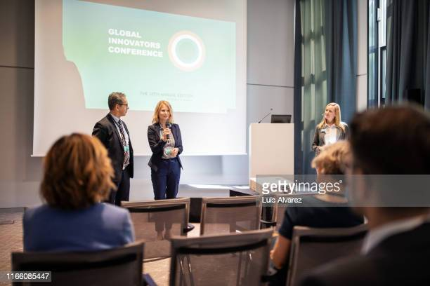 businesswoman giving speech at launch event - mittelgroße personengruppe stock-fotos und bilder