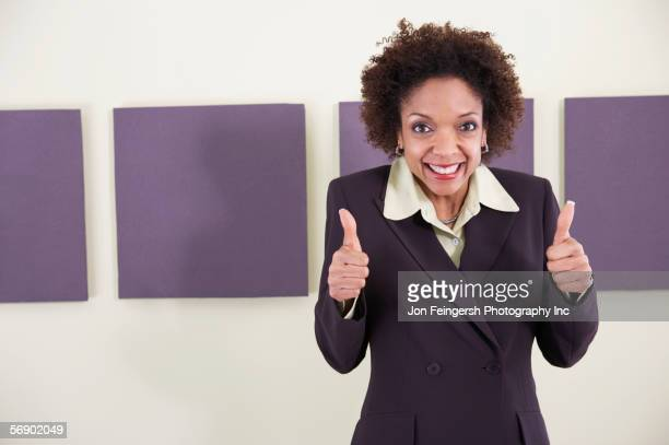 Businesswoman giving thumbs up sign