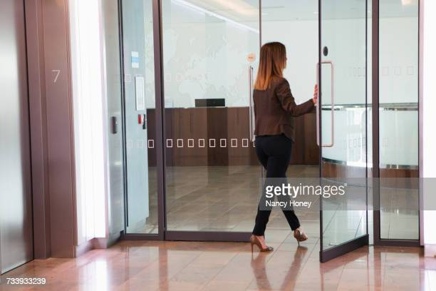 Businesswoman going through office door