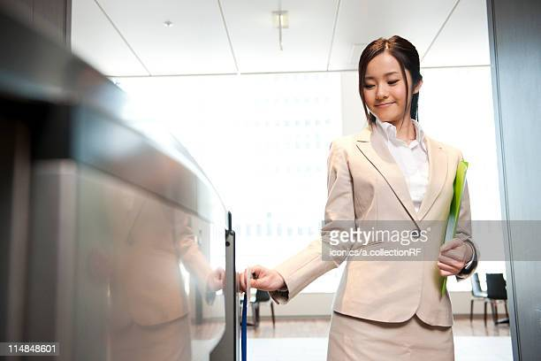 Businesswoman going through security turnstile, Tokyo Prefecture, Honshu, Japan