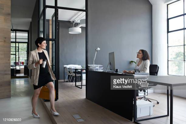 businesswoman greeting to coworker at workplace - cream coloured blazer stock pictures, royalty-free photos & images