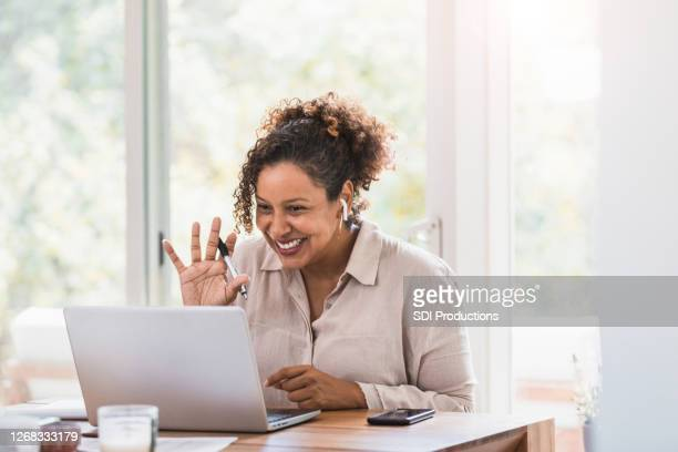 businesswoman greets colleagues during virtual meeting - waving stock pictures, royalty-free photos & images