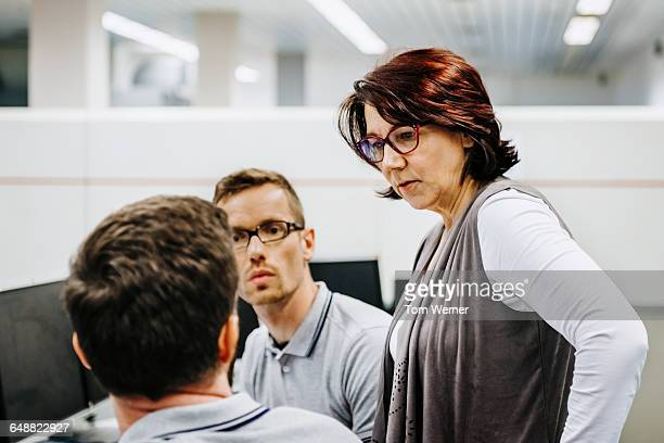 Businesswoman guiding engineers in a control room