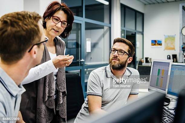 businesswoman guiding engineers in a control room - control room stock pictures, royalty-free photos & images