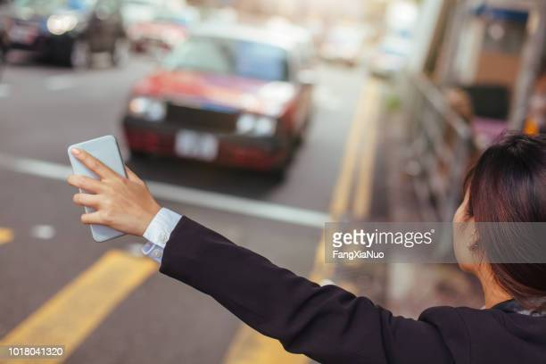 businesswoman hailing taxi in city - hail stock pictures, royalty-free photos & images