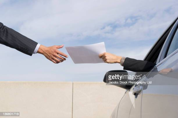 Businesswoman handing paperwork to co-worker from car