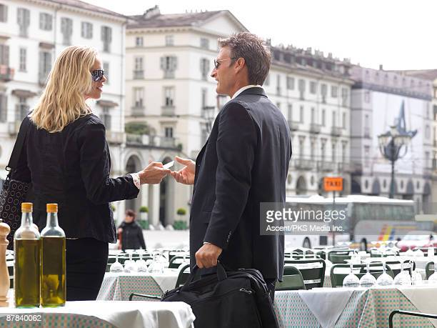 Businesswoman hands card to businessman, at cafe