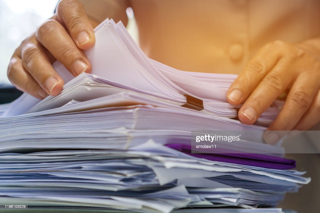 Businesswoman hands working in Stacks of paper files for searching information on work desk office, business report papers,piles of unfinished documents achieves with clips indoor,Business concept : Stock Photo
