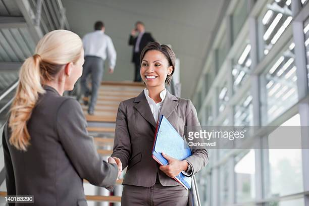 businesswoman handshaking on stairs - deal england stock photos and pictures