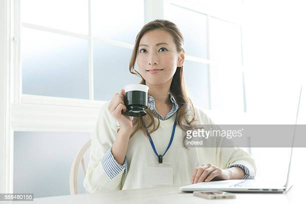 Businesswoman having a coffee at table