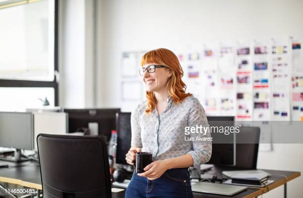 businesswoman having a coffee break in office - espontânea imagens e fotografias de stock