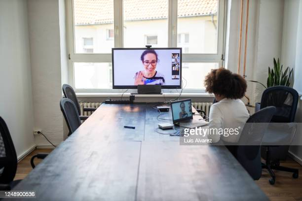 businesswoman having a meeting with coworkers over a video call - テレビ会議 ストックフォトと画像