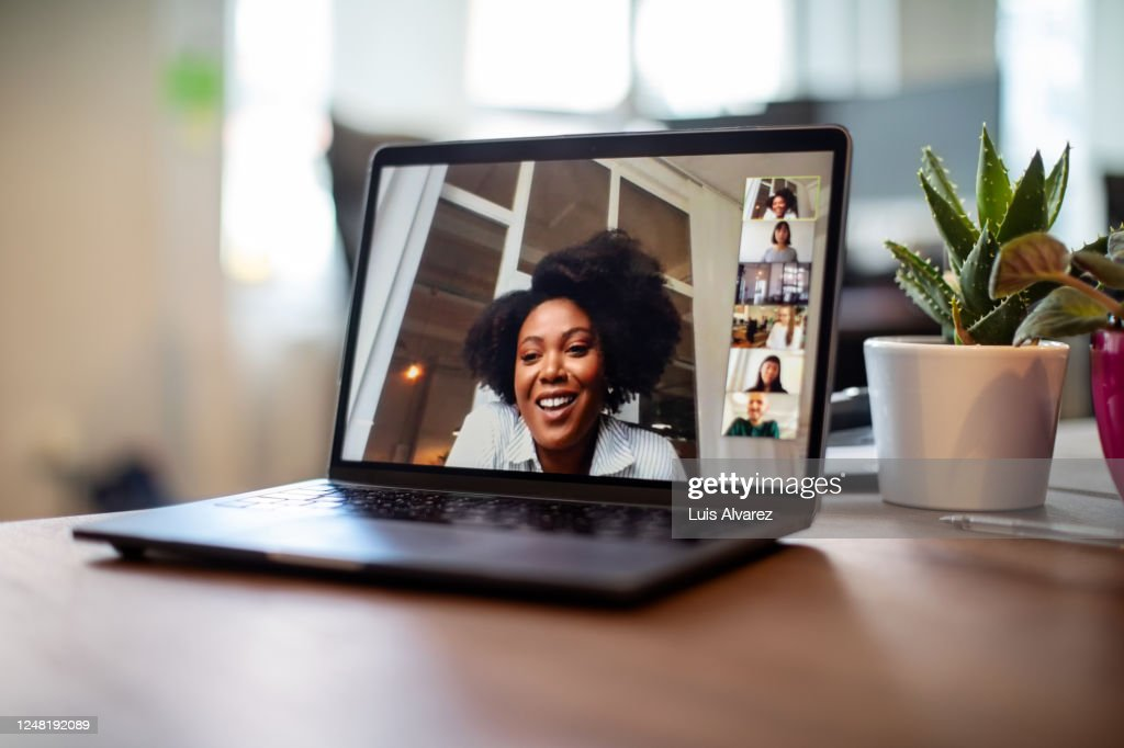 Businesswoman having a video call meeting with her team : Stock Photo