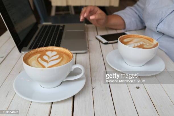 Businesswoman Having Cappuccino While Using Laptop On Table At Cafe