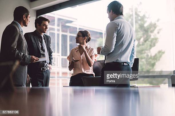 businesswoman having discussion with colleagues in office - bedrijven financiën en industrie stockfoto's en -beelden