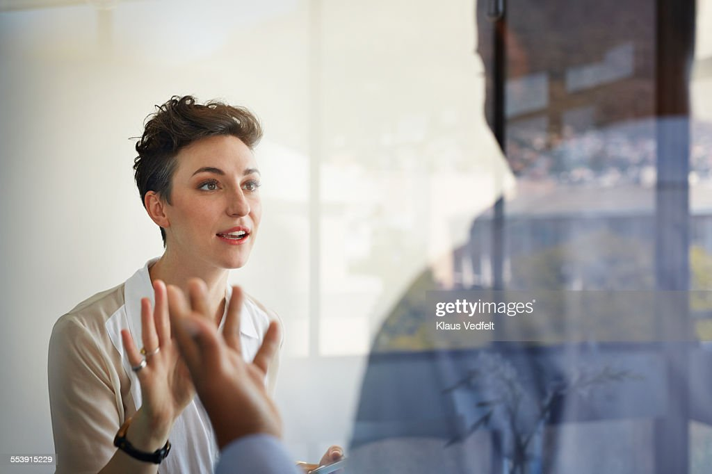 Businesswoman having discussion with male coworker : Stockfoto