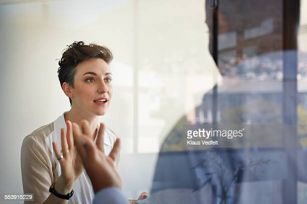 businesswoman having discussion with male coworker - konflikt stock-fotos und bilder